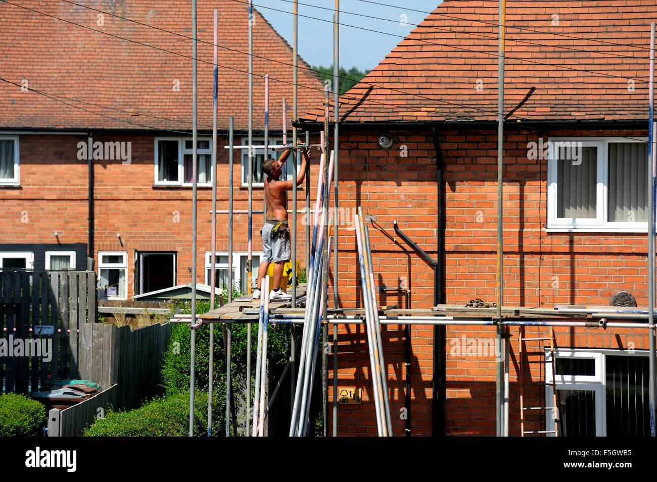 Scaffolding being erected on a semi detached house England uk - Stock Image