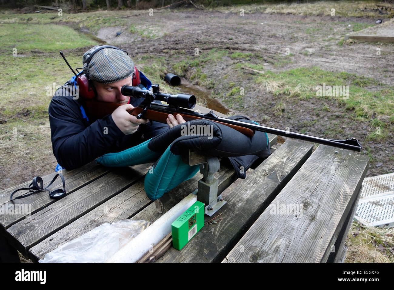 Hunter with hunting rifle equipped with a scope is about to shoot a training round. - Stock Image