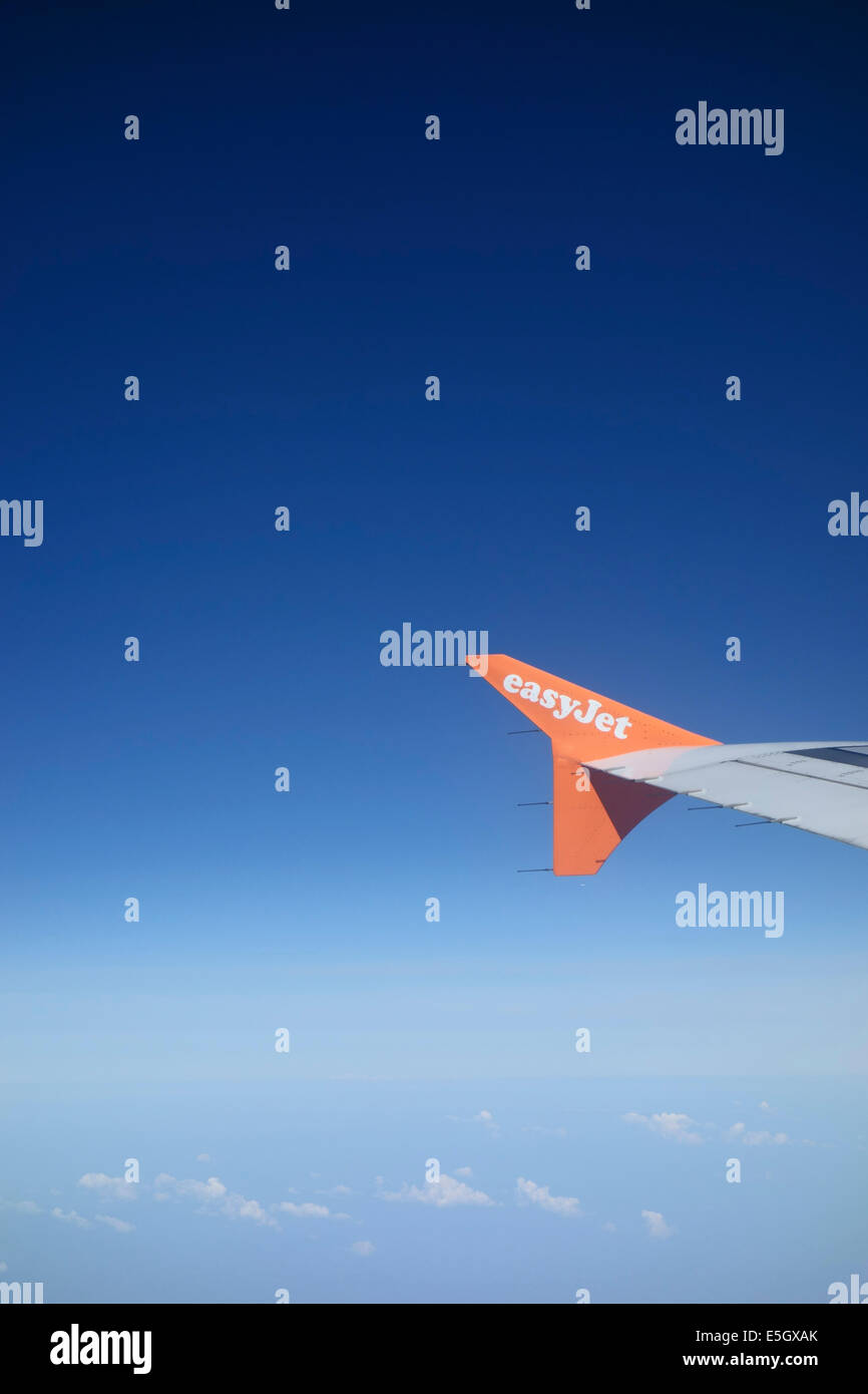 View from aeroplane window showing Easyjet insignia on the wing. - Stock Image