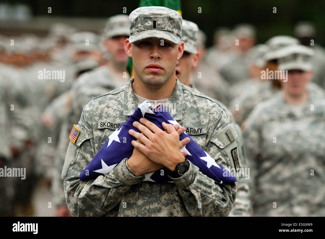 A U.S. Soldier assigned to the Army Reserve 423rd Military Police (MP) Company holds an American flag, accompanied - Stock Image
