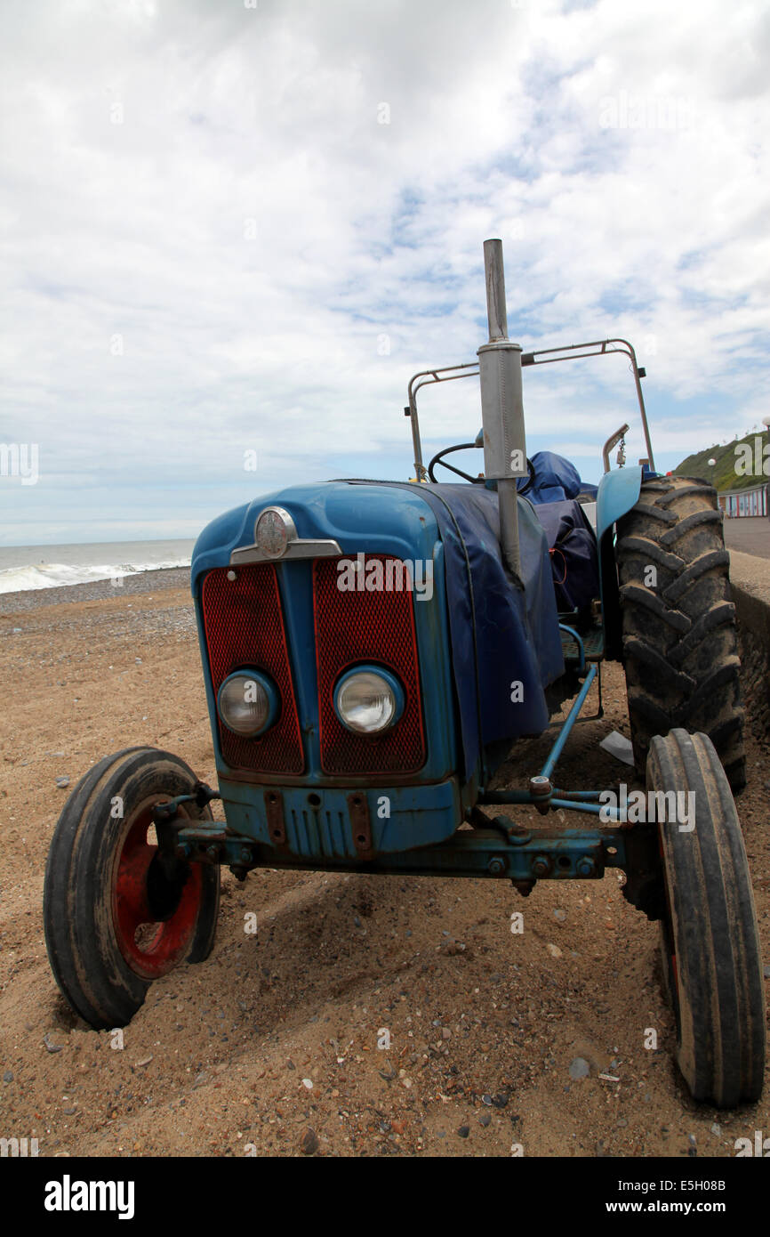 An ancient tractor on a Norfolk beach, used to pull the fishing boats in and out of the water - Stock Image