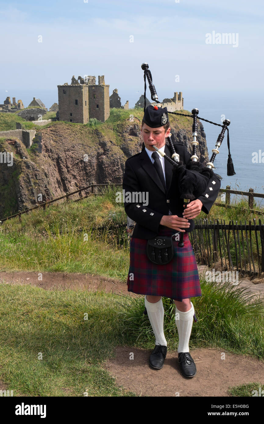 Piper playing pipes in traditional Scottish kilt at Dunnottar Castle in Aberdeenshire Scotland UK - Stock Image