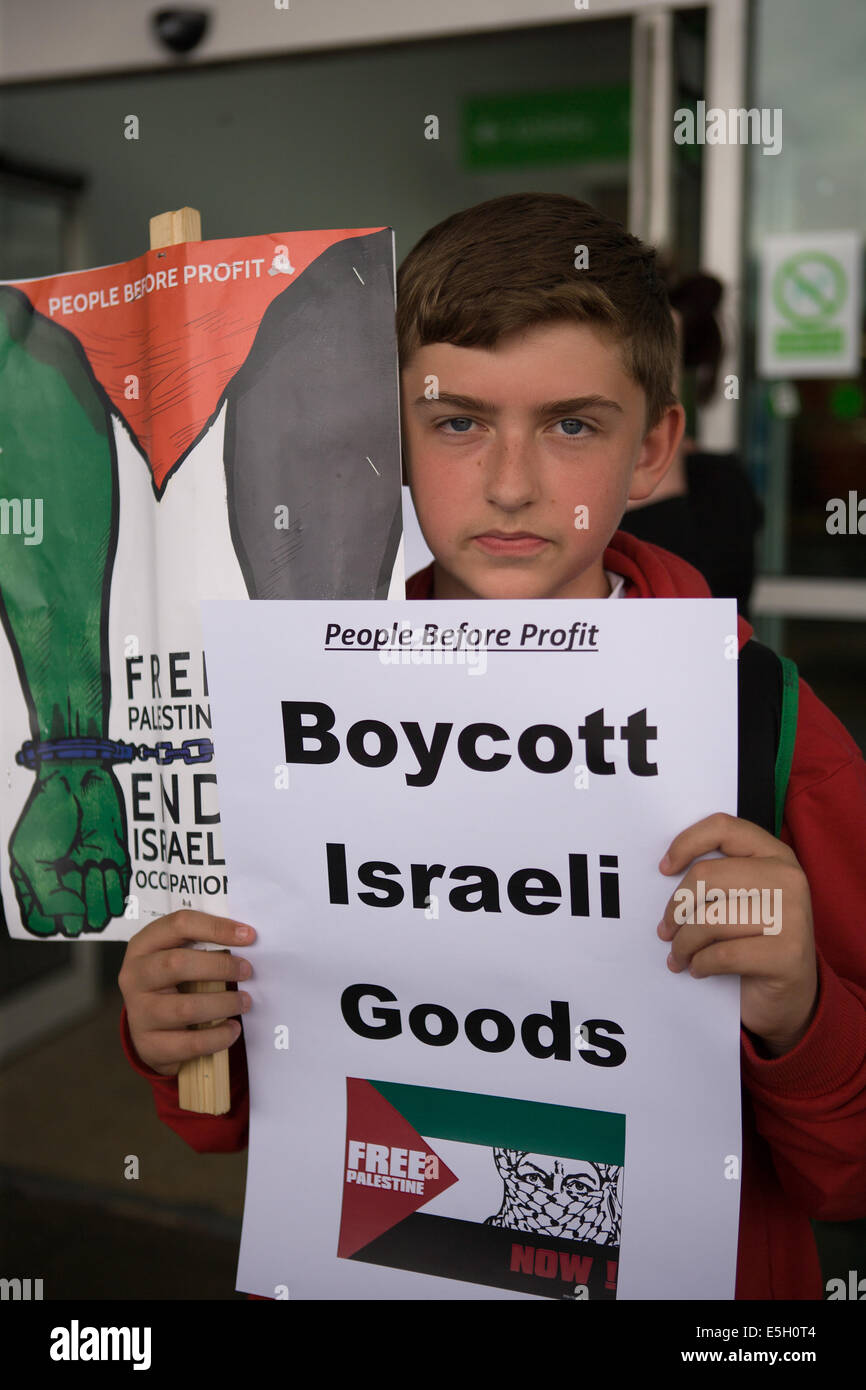 Andersonstown Rd, West Belfast, Ireland. 31st July, 2014. A boy holding a 'Boycott Isralei Goods' poster - Stock Image
