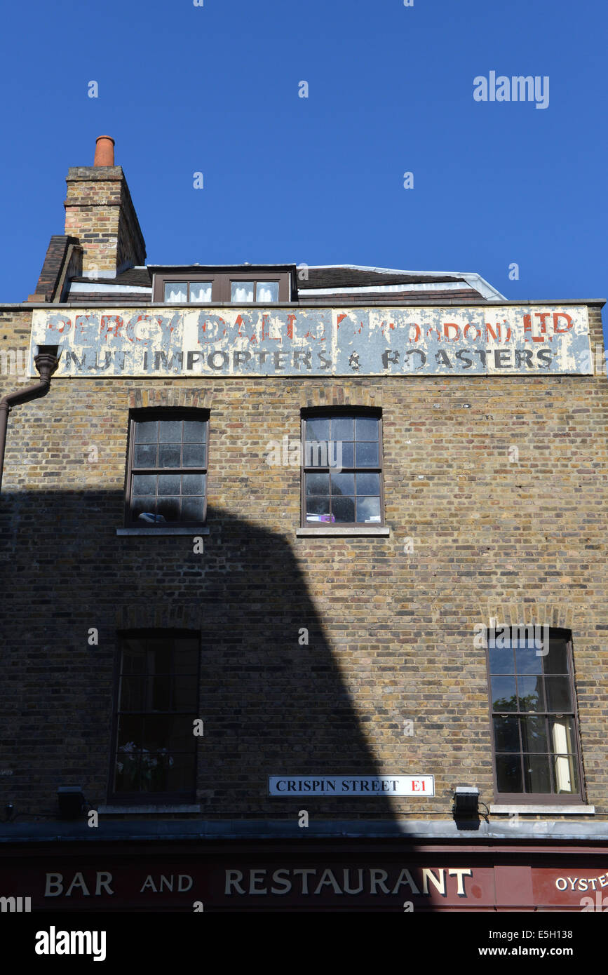 Percy Dalton peanut roasters importers advert faded worn painted top building Crispin street shoreditch London - Stock Image