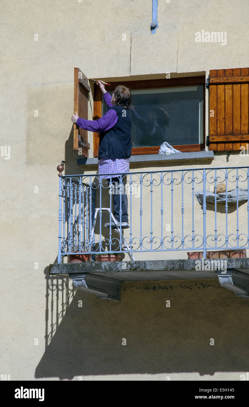 An old woman is painting her wooden shutters, blinds. She is on stepladder put on her balcony. Stock Photo