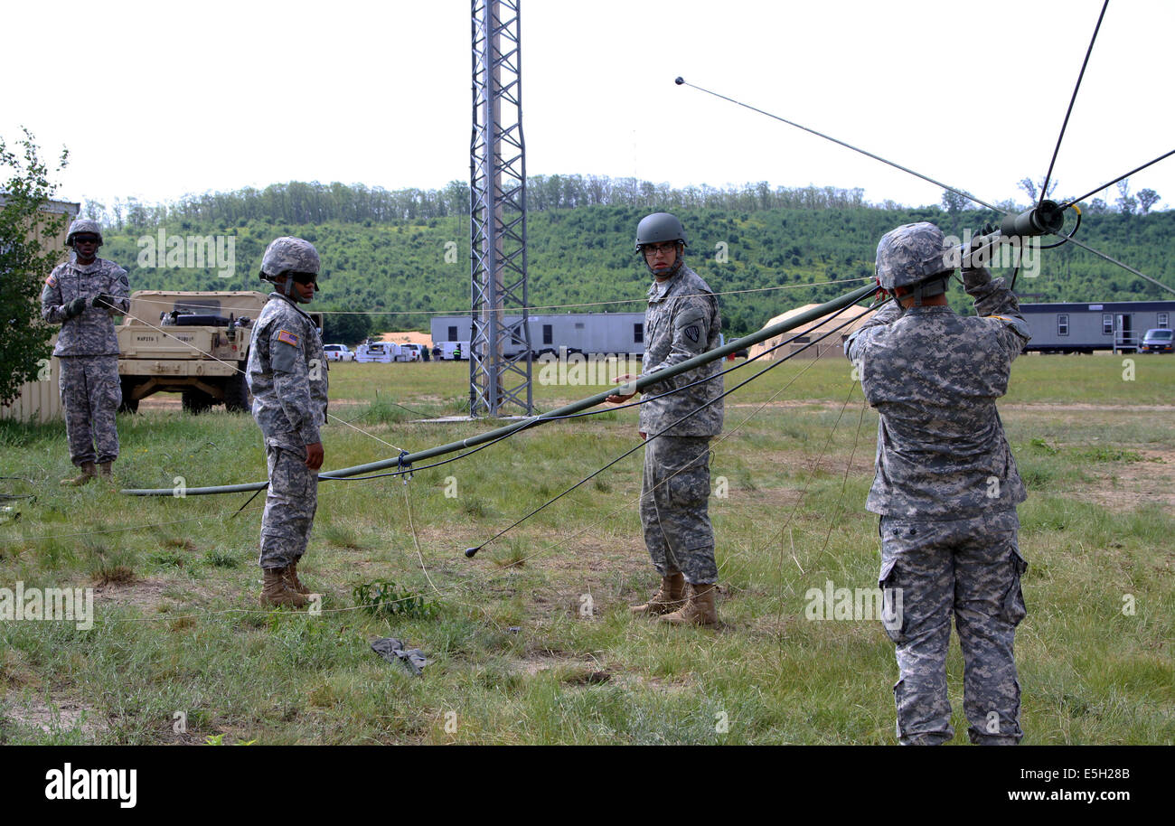 U.S. Soldiers with the 187th Signal Company, New York Army National Guard, raise an OE254 antenna during scenario Stock Photo