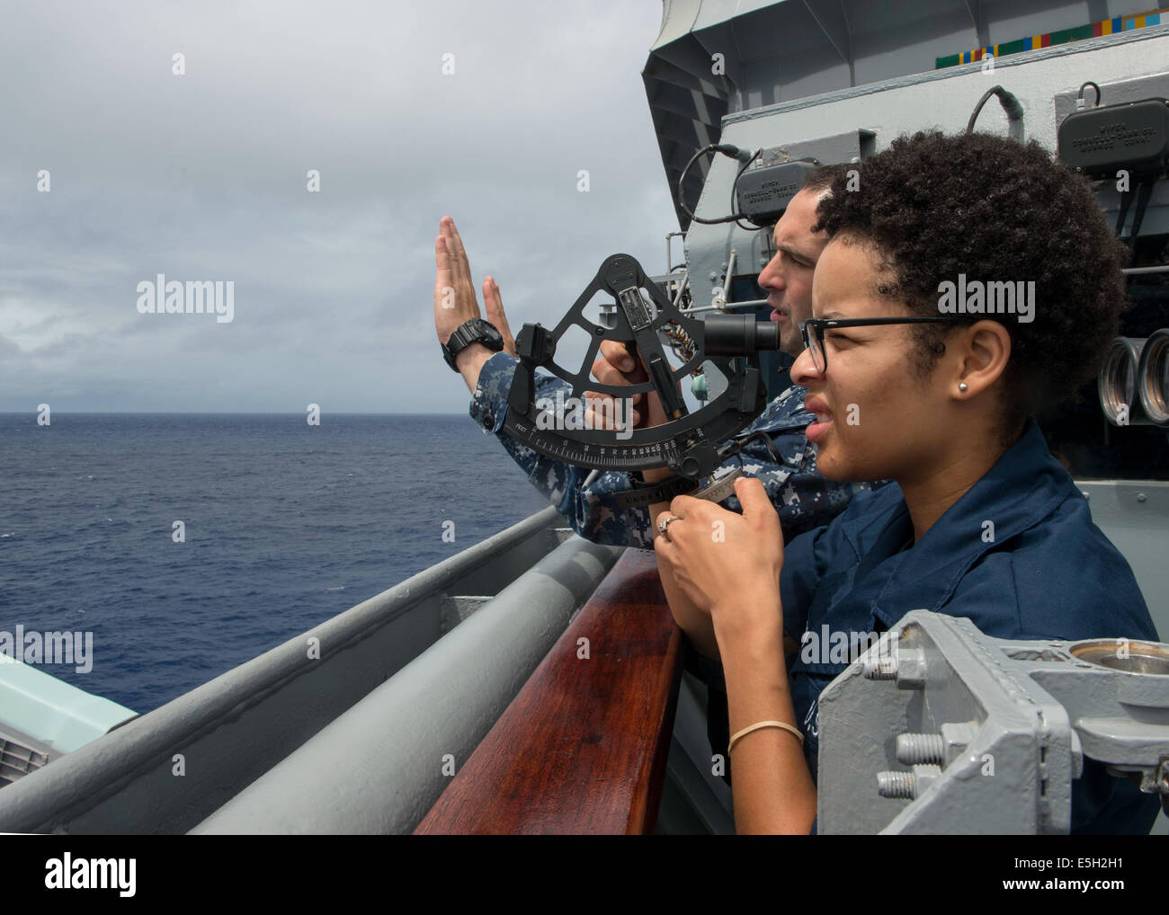 U.S. Navy Quartermaster 1st Class Clarence Ilijic, left, teaches Quartermaster Seaman Eden Boyd how to operate a - Stock Image