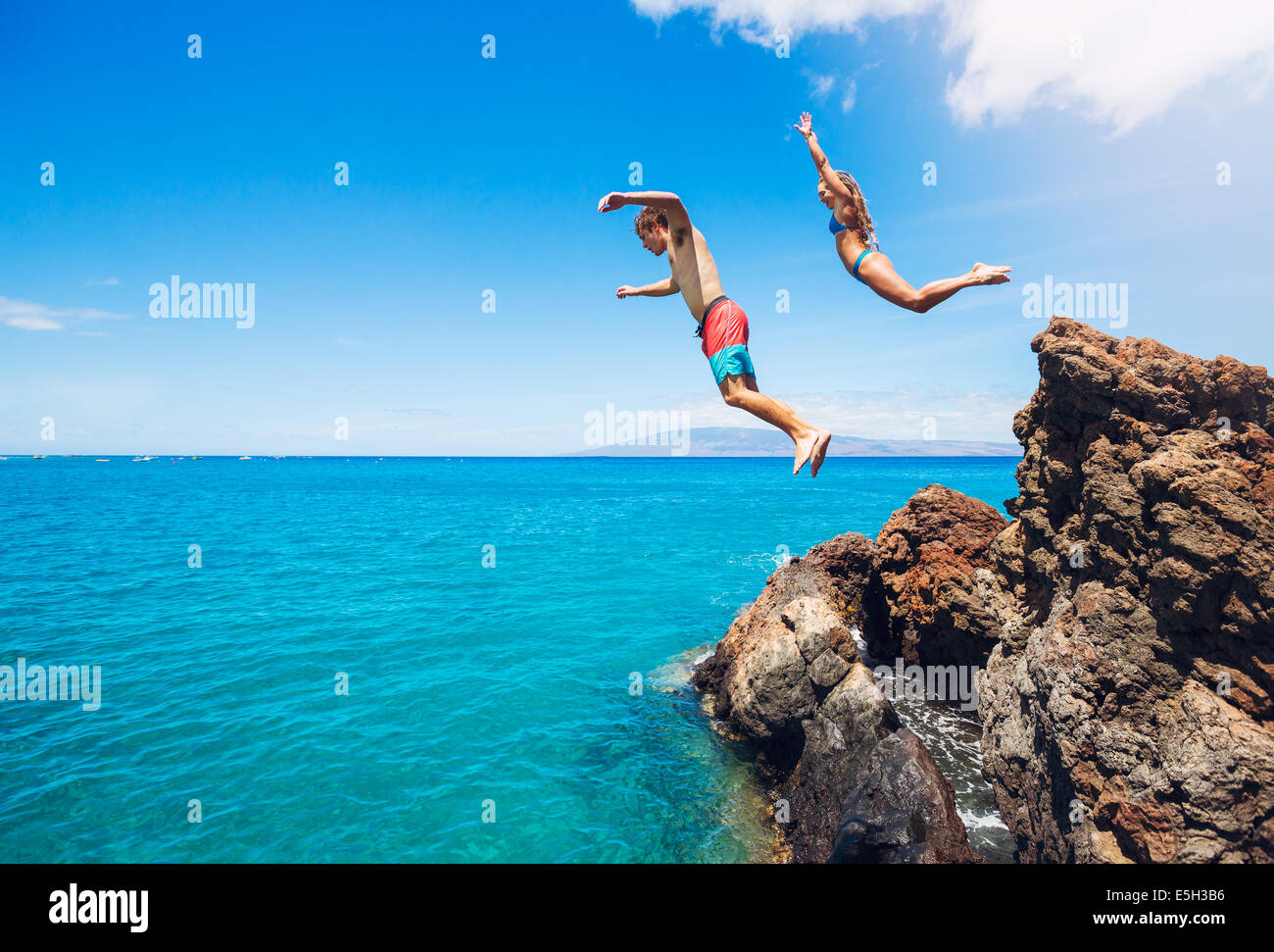 Friends cliff jumping into the ocean, summer fun lifestyle. - Stock Image