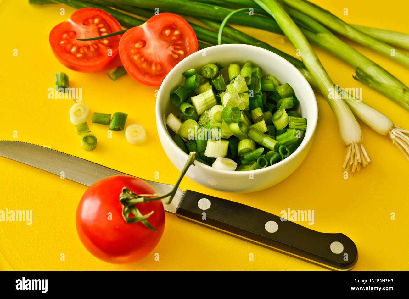 Fresh vegetables on a cutting board with a knife - Stock Image