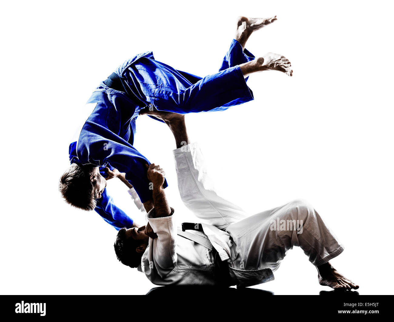 two judokas fighters fighting men in silhouette on white background - Stock Image