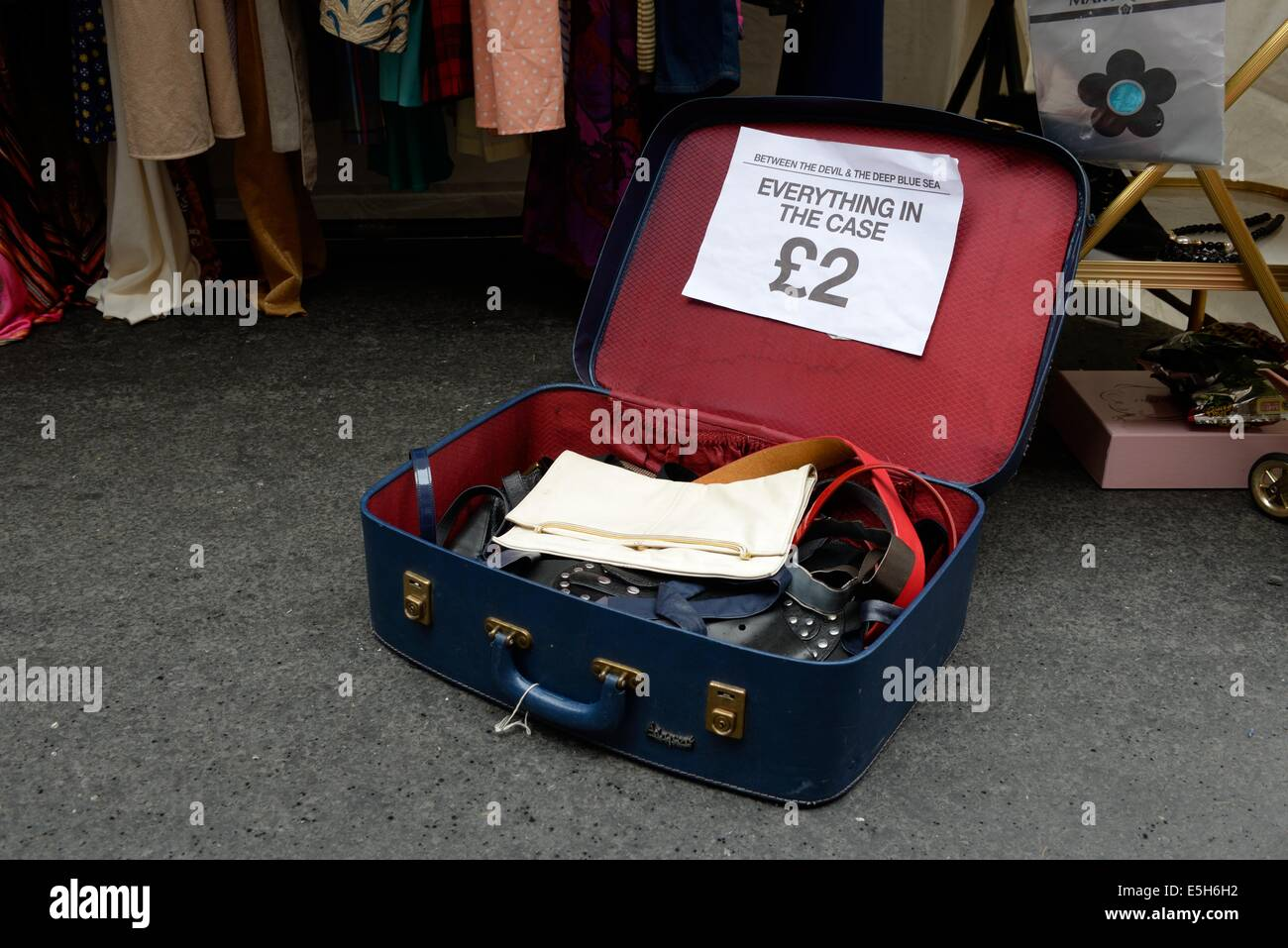 A secondhand suitcase containing items priced at £2 open on the ground at an outdoor market stall in Glasgow, - Stock Image