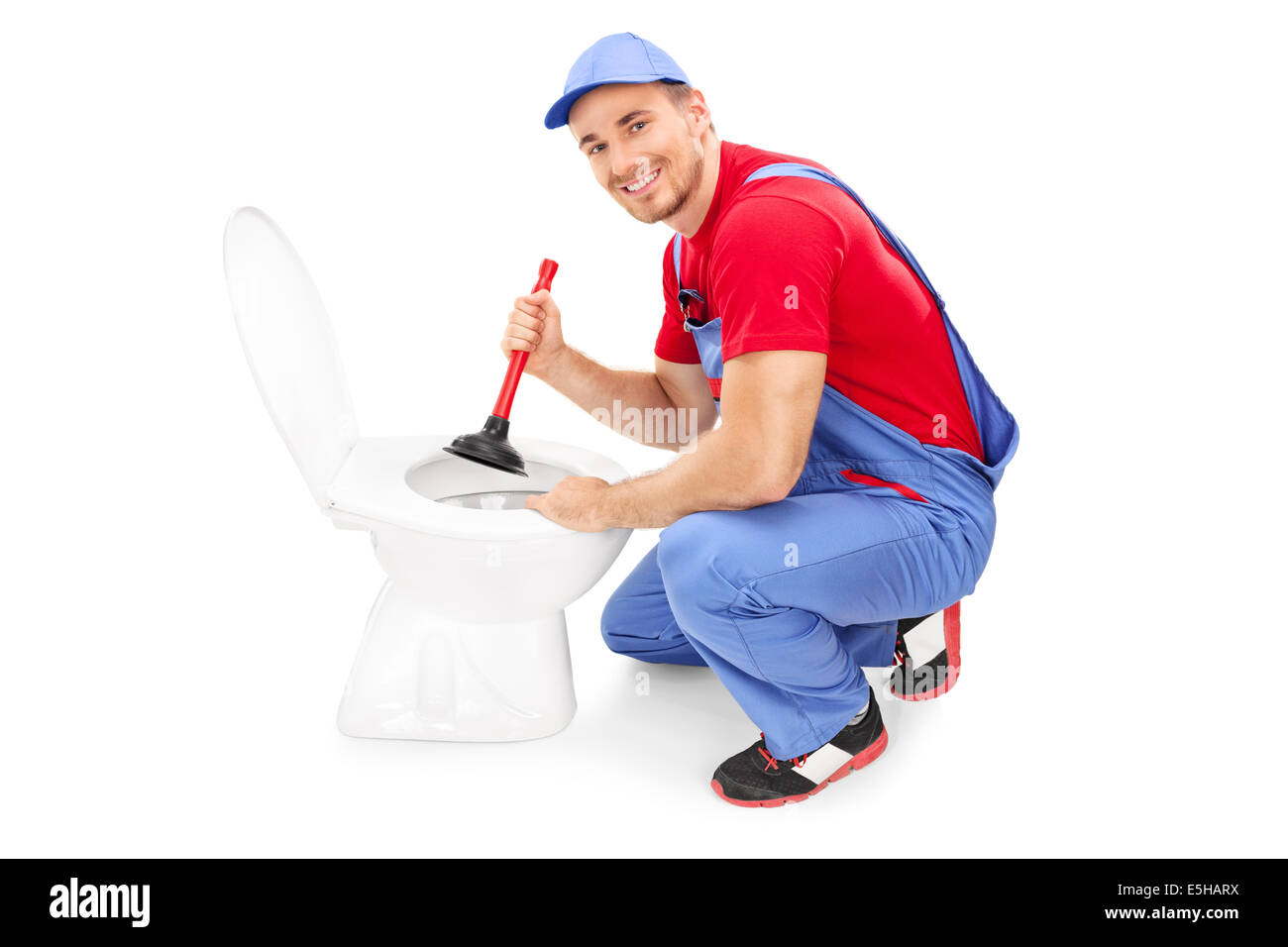 Male plumber unclogging a toilet with a plunger Stock Photo ...