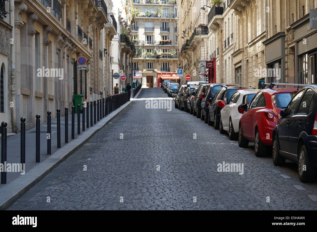 Paris street around with buildings, with black railings separating sidewalk and road on the left, cars parked on - Stock Image