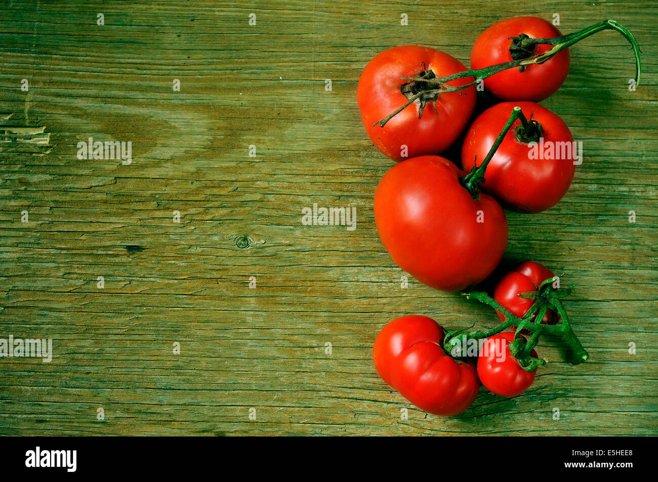 a bunch of ripe tomatoes on a rustic wooden table, with a filter effect - Stock Image