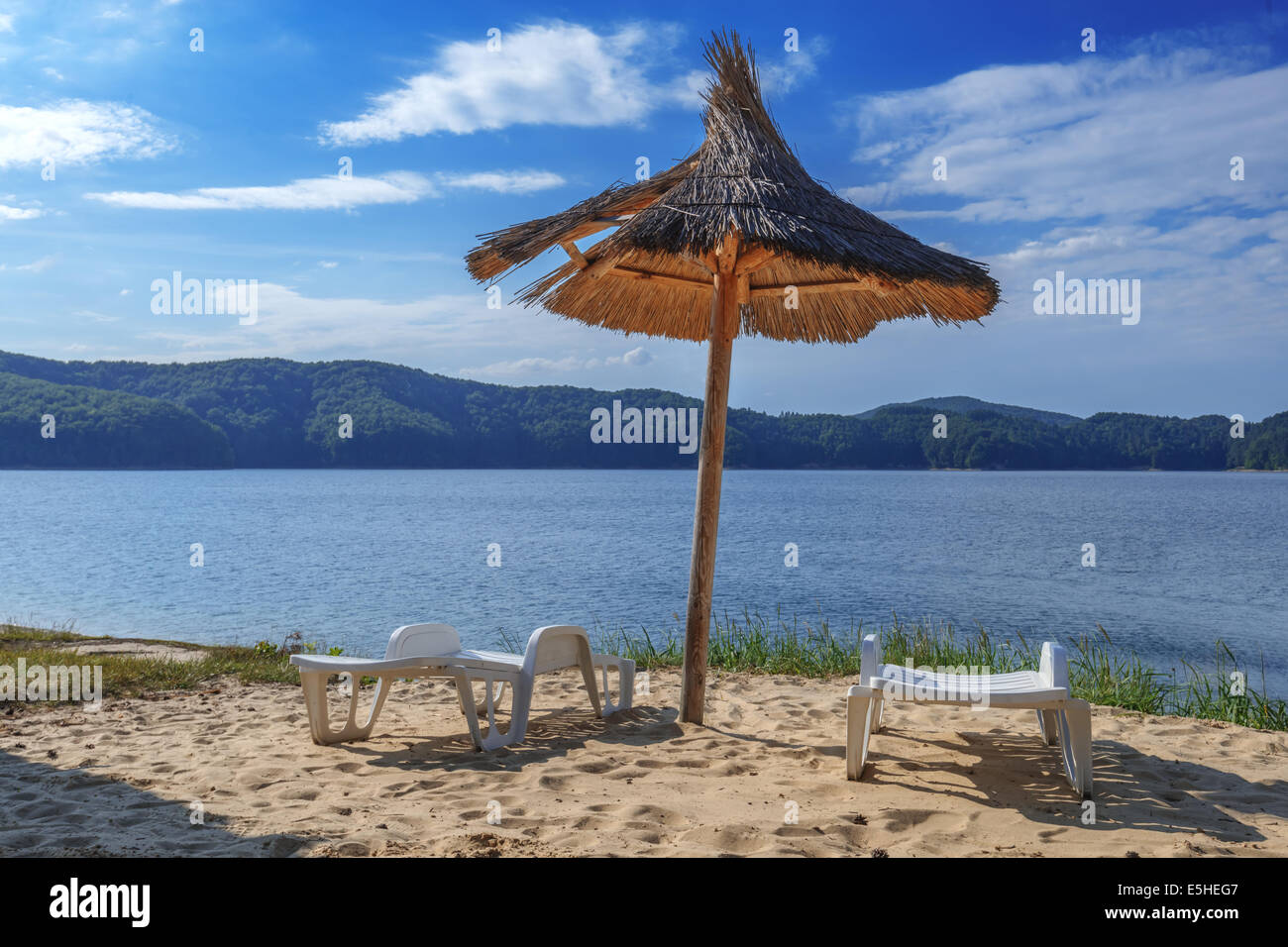 deck-chair and parasol on beach - Stock Image