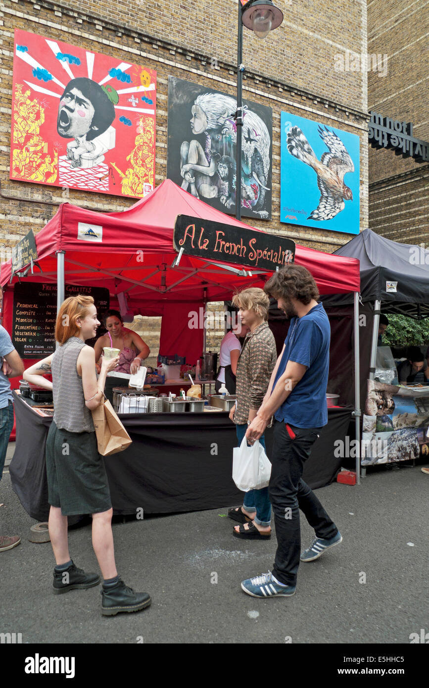 Young people drink coffee and talk at a French street food market stall  in Whitecross Street, Islington, East London - Stock Image
