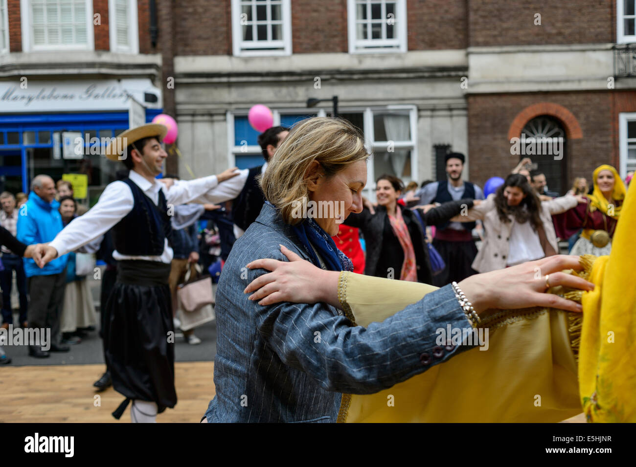 Member of the public female woman joins in with a Greek syrtaki dance troupe at Marylebone Street Summer Fayre fair, - Stock Image