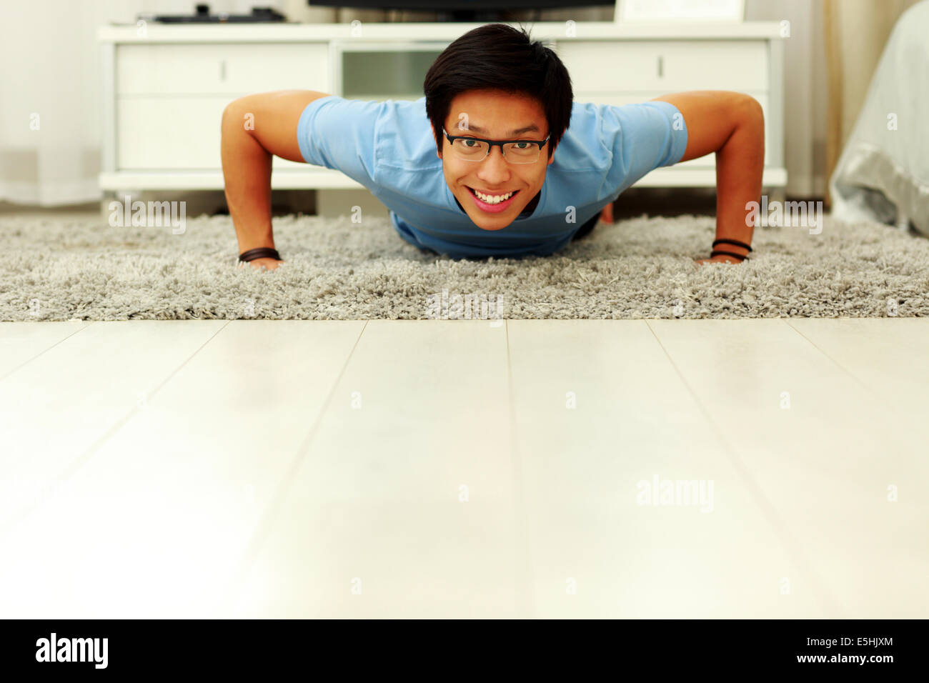 Portrait of a sporty young man doing push ups in the living room at home - Stock Image