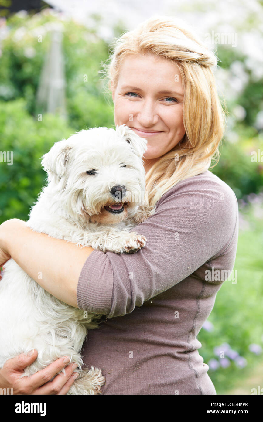 Portrait Of Woman With Pet Dog In Garden Stock Photo