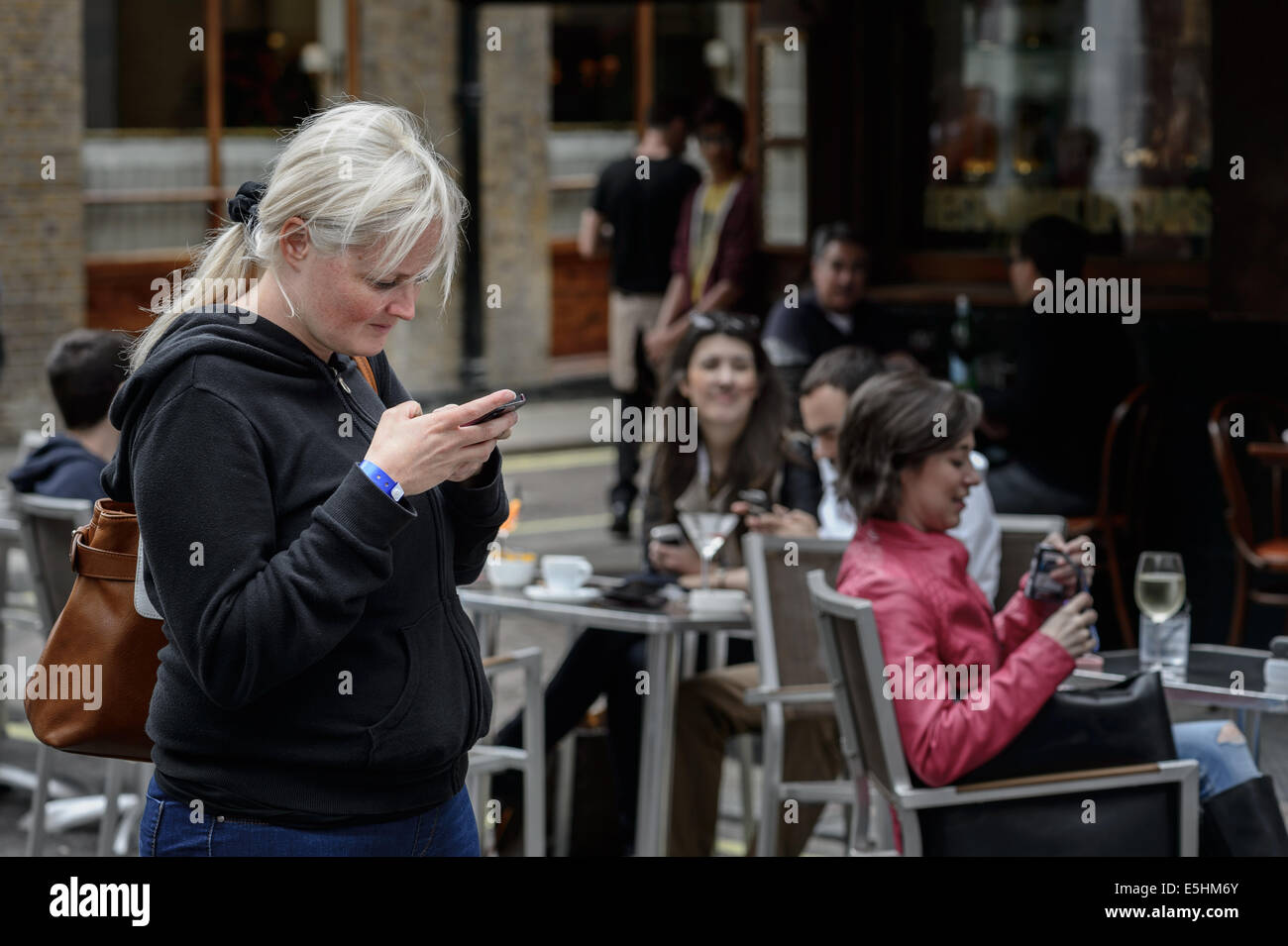 British blonde white woman sends reads a text message sms email on a smartphone smart phone. - Stock Image