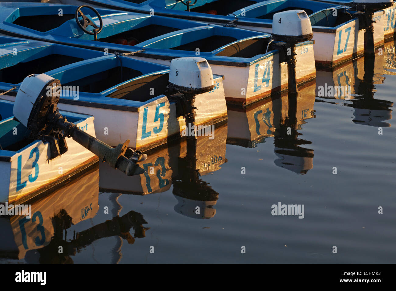 motors on boats for hire on the River Stour at Christchurch Town Quay, Dorset, UK in the evening light in July - Stock Image