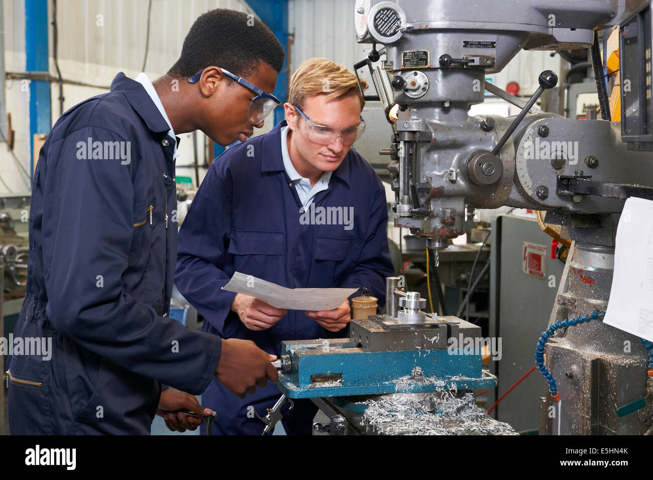 Engineer Showing Apprentice How to Use Drill In Factory - Stock Image