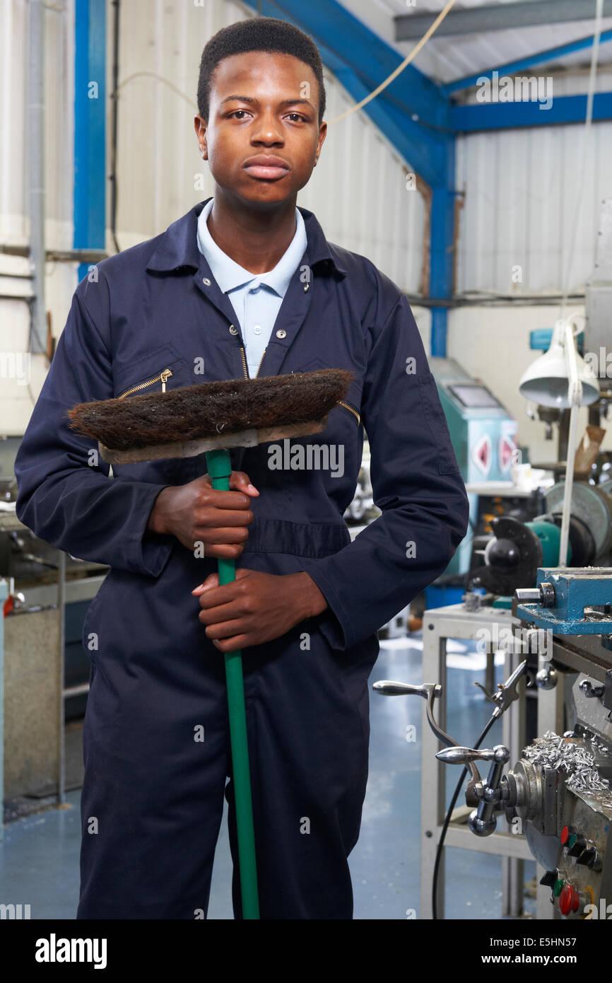 Apprentice In Engineering Factory Sweeping Floor - Stock Image