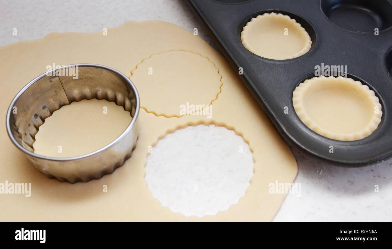 Cutting large circles of pastry to line a bun tin Stock Photo