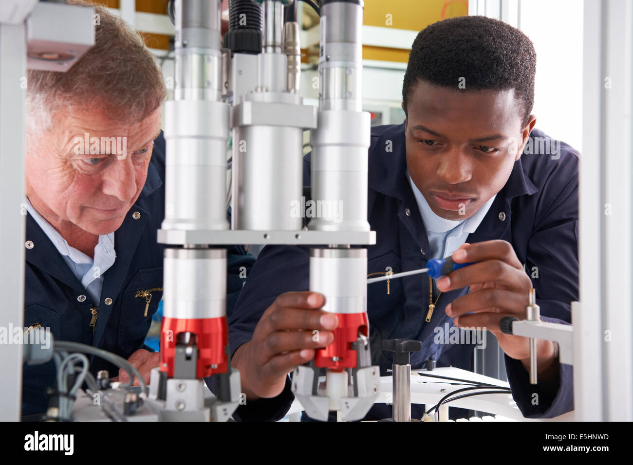 Engineer And Apprentice Working On Machine In Factory - Stock Image
