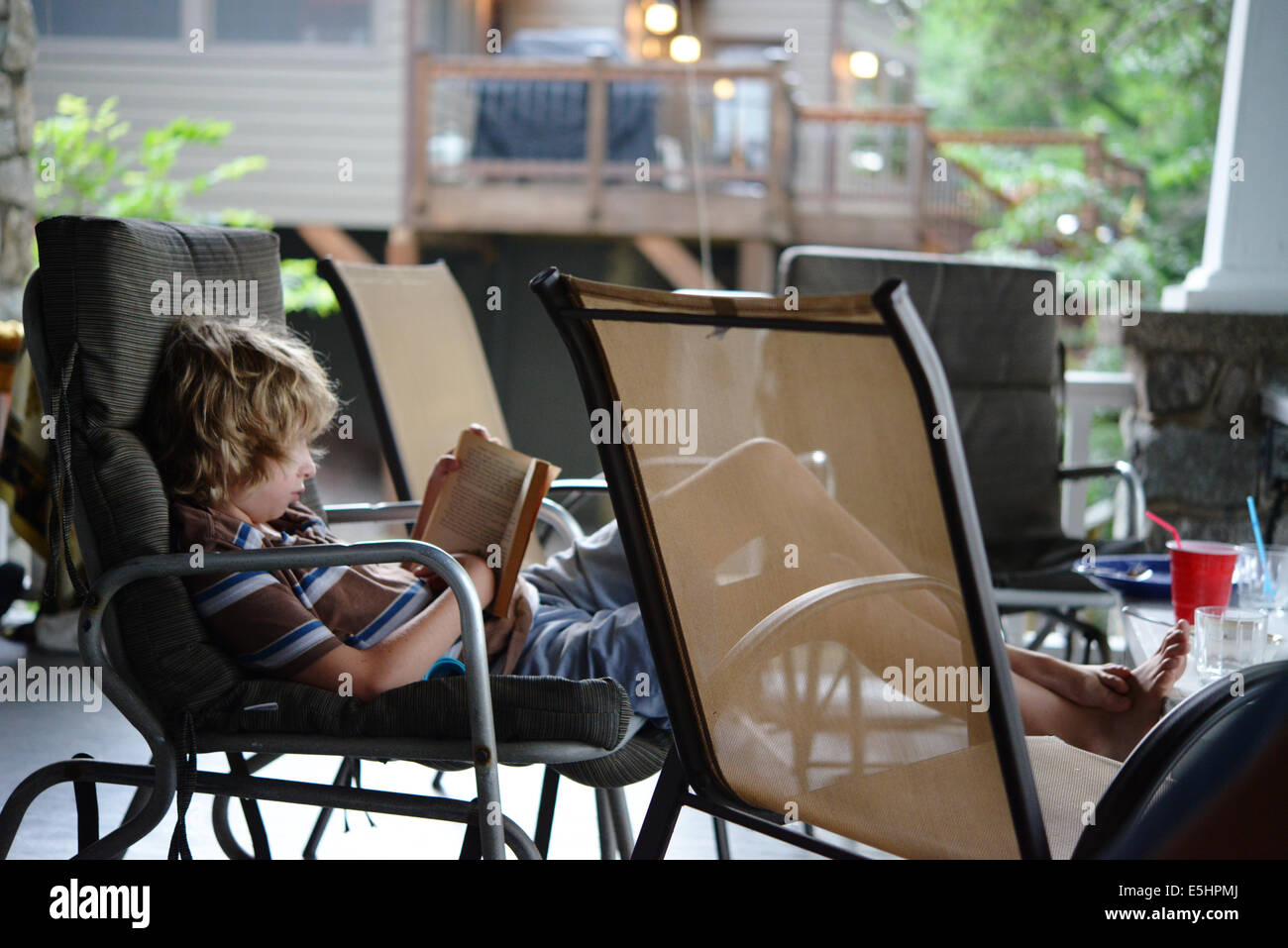 Blond hair kid reading on porch - Stock Image