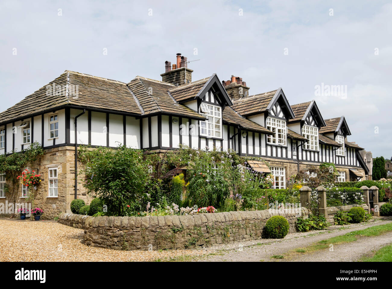 Row of 19th century Tudor style terraced houses (1882) with cottage gardens in summer. Whalley, Lancashire, England, - Stock Image