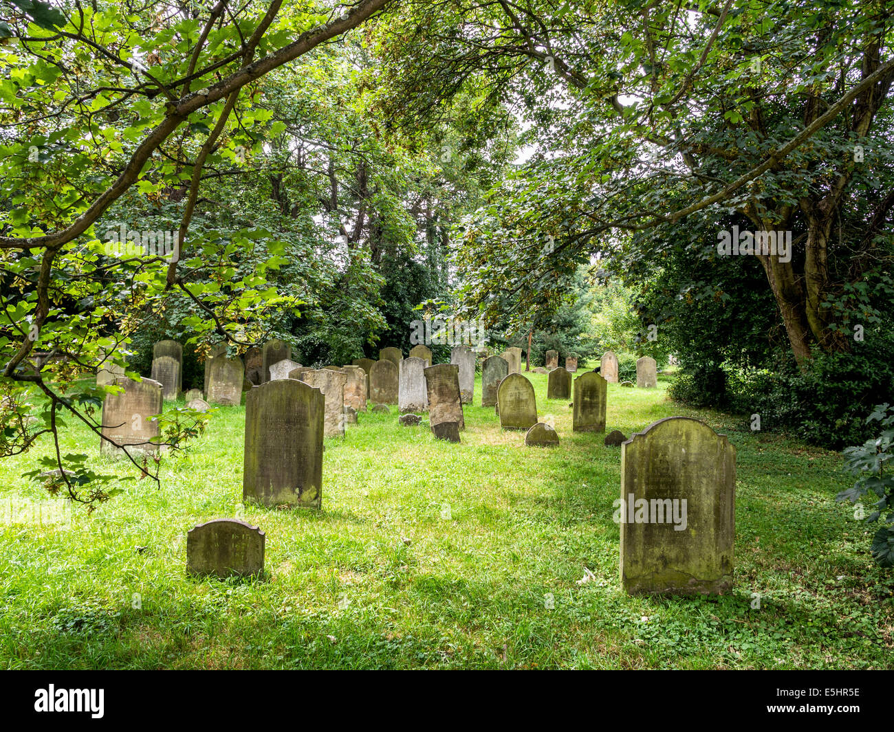 Old Cemetery and graveyard with weathered tombstones in a leafy burial ground - Twickenham, London, UK - Stock Image