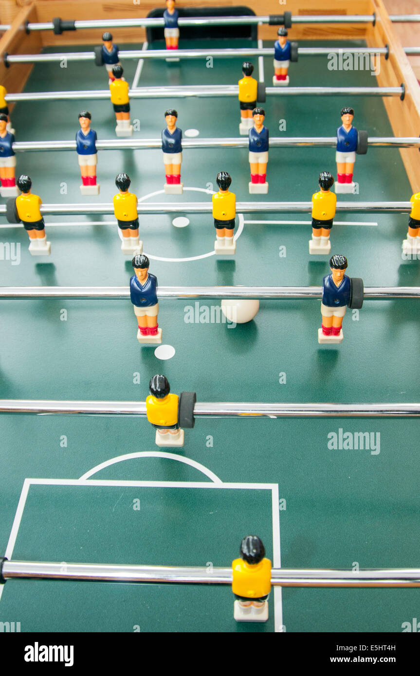 a table football match between the blue and yellow teams - Stock Image
