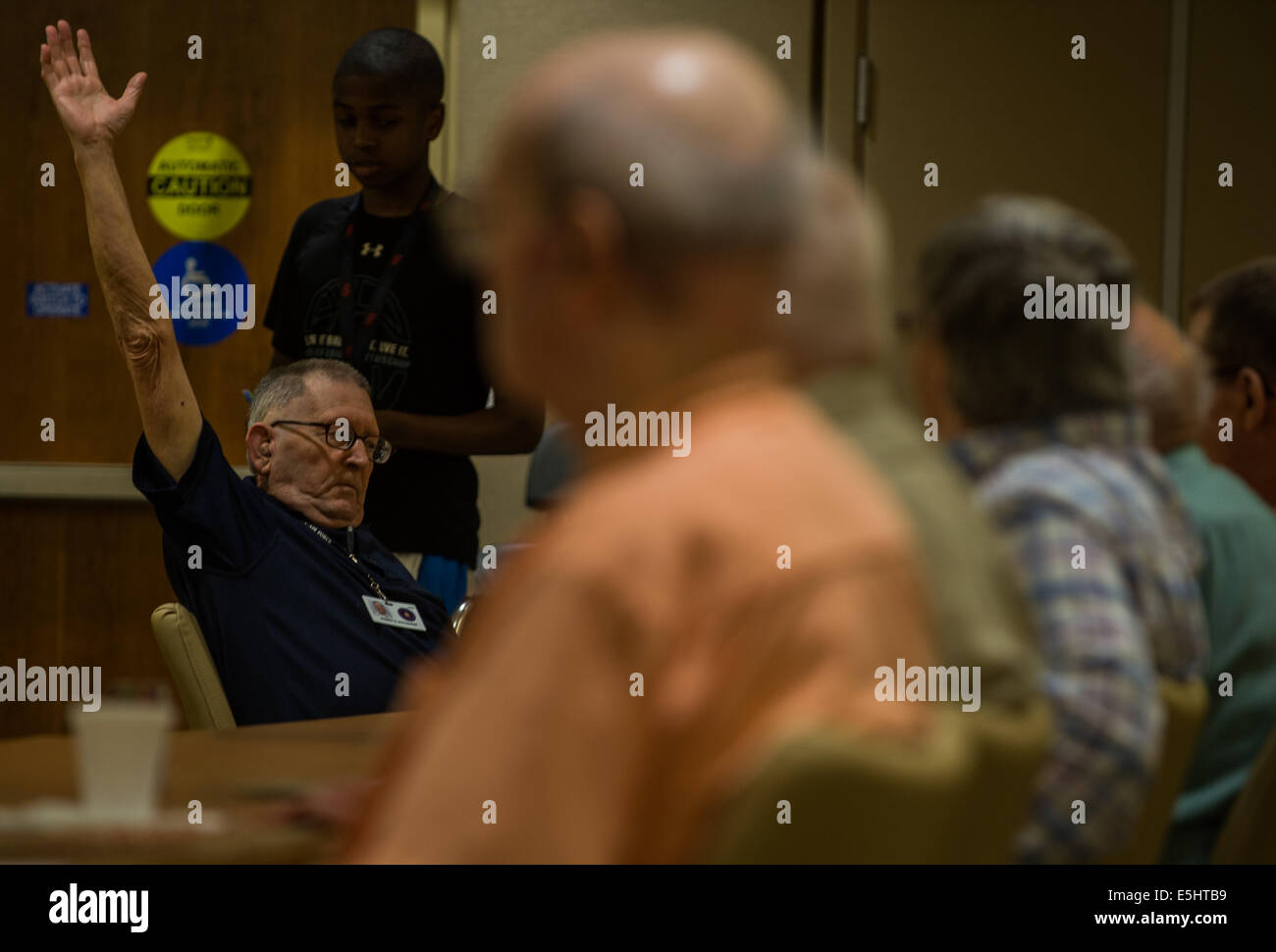 A retired military veteran raises his hand  in celebration during a bingo game June 18, 2014, at the Armed Forces Stock Photo