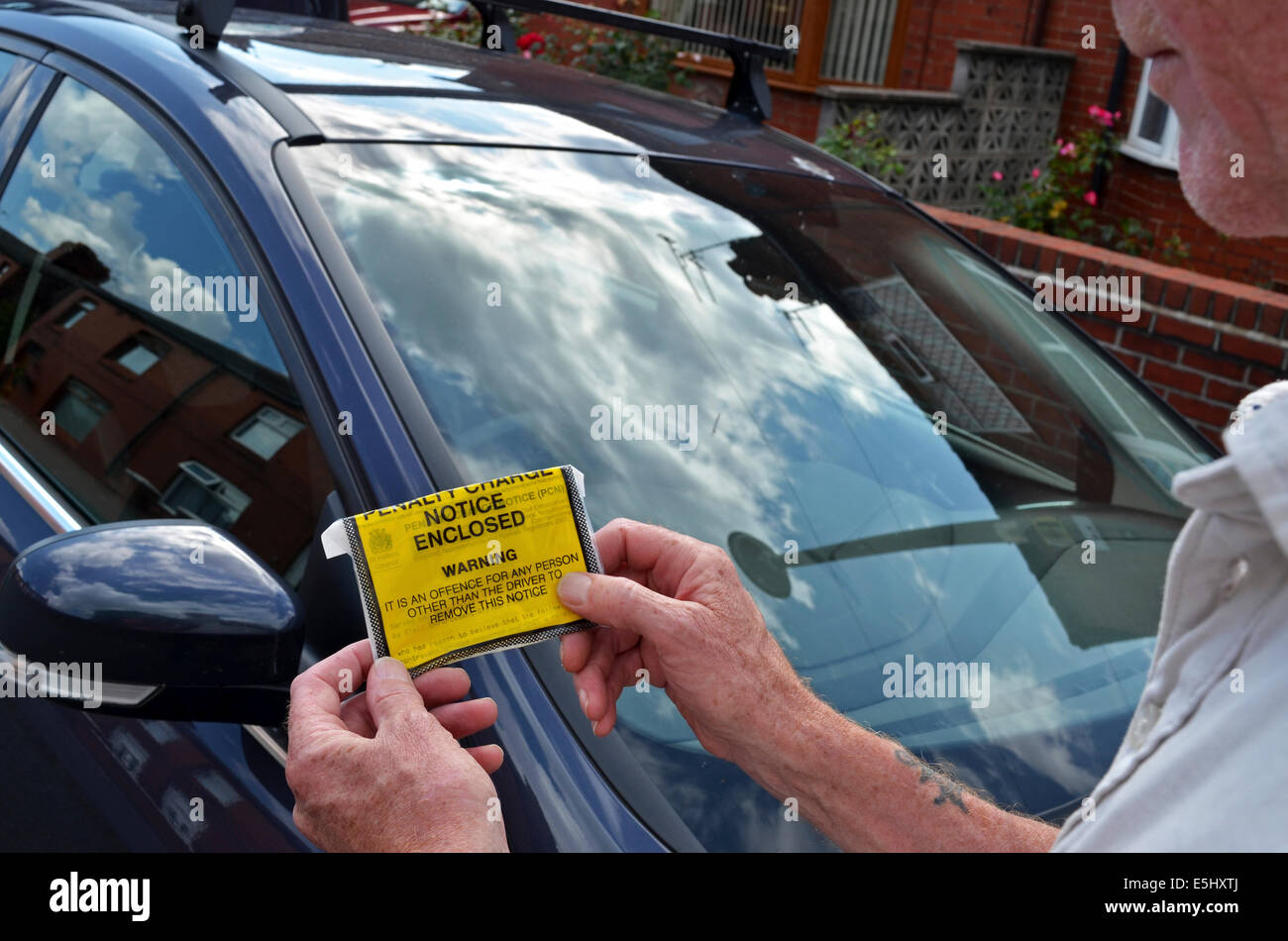 A driver taking a Penalty Charge ticket off his vehicle - Stock Image