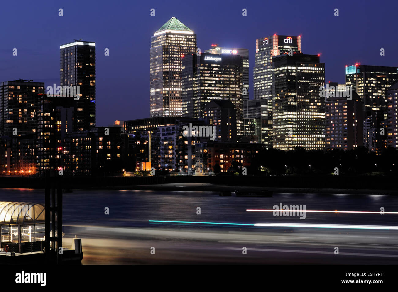 Canary Wharf London UK illuminated at night, with river