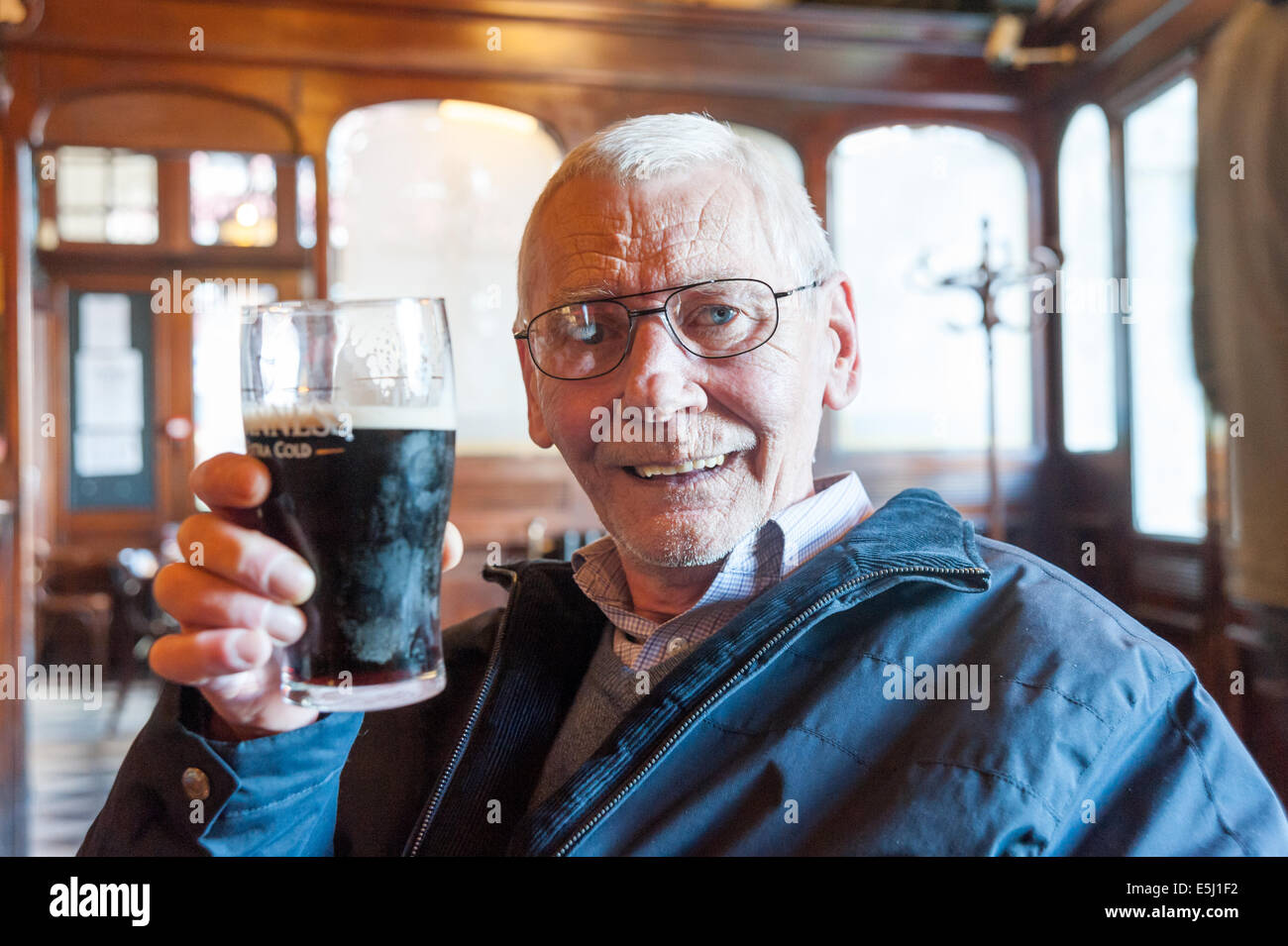 Elderly man drinking pint of Guinness in a pub, UK - Stock Image