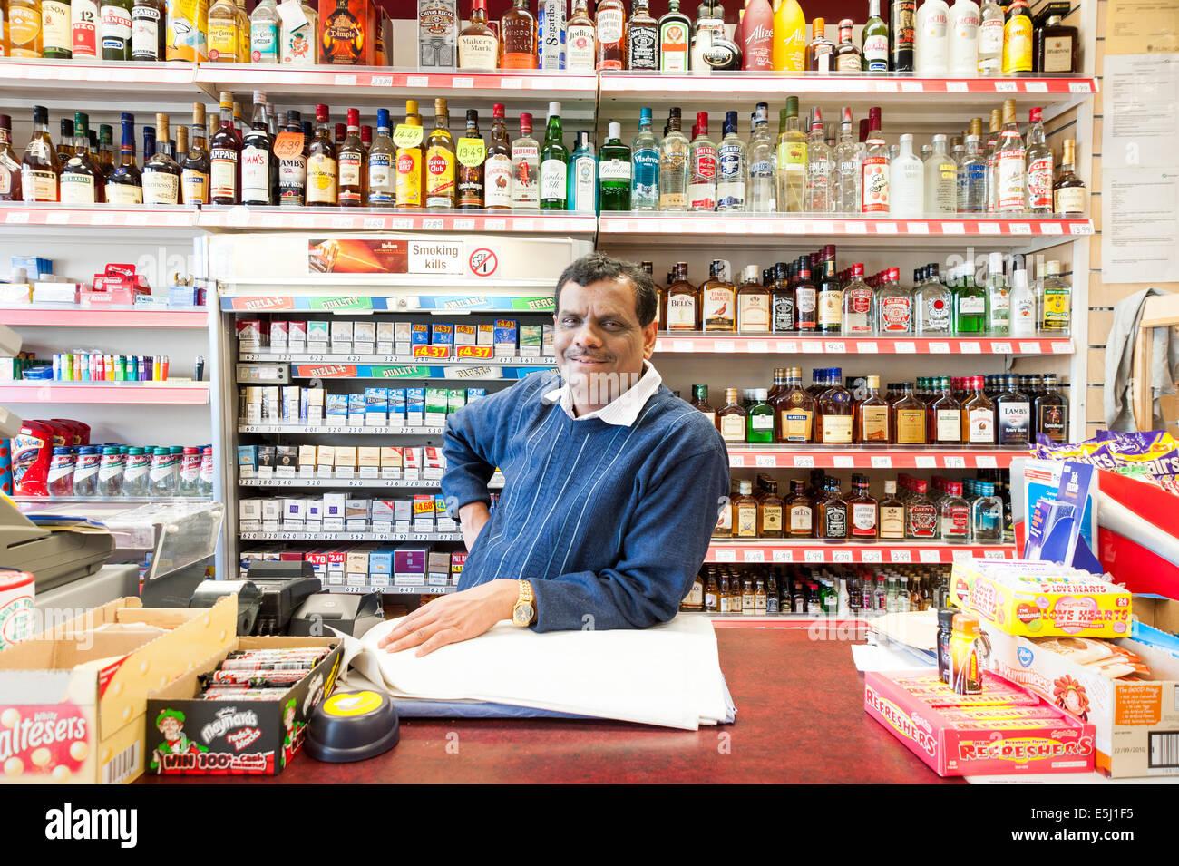 Portrait of Indian off-licence owner, London, England, UK - Stock Image