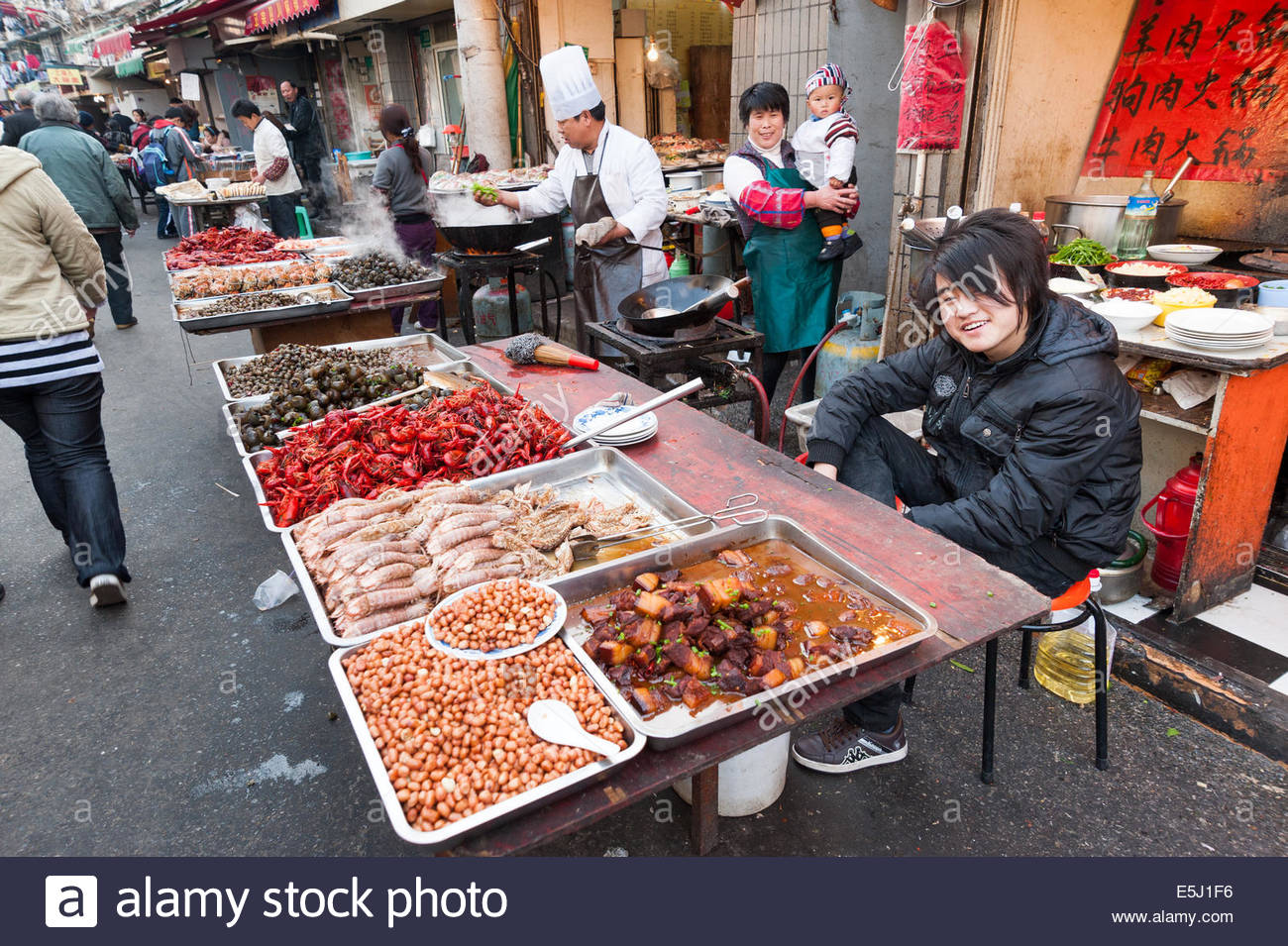 Aspirational teenager on his parents market stall selling street food in the Old City, Shanghai, China - Stock Image