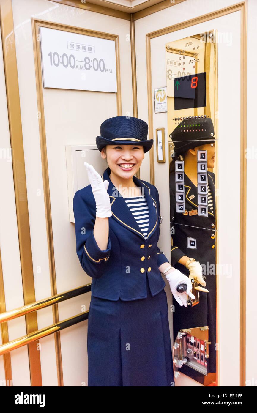 Lift operator in Takashimaya department store, Tokyo, Japan - Stock Image
