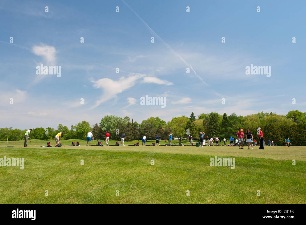 Golfers practicing their swing on a driving range. - Stock Image