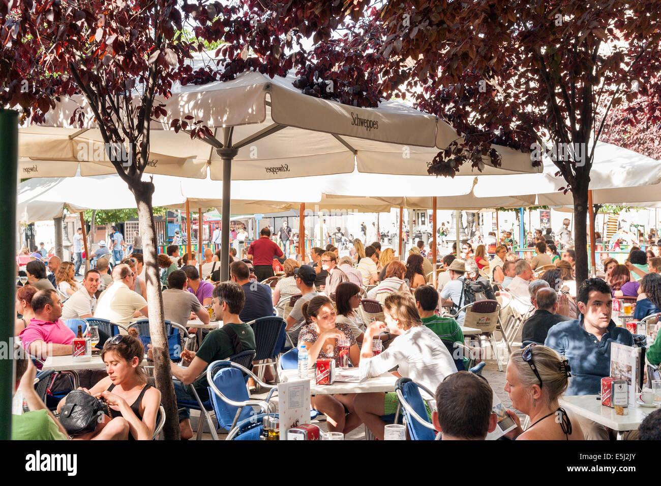People at crowded bar tables on Plaza de Santa Ana, Barrio de las Letras, Madrid, Spain - Stock Image