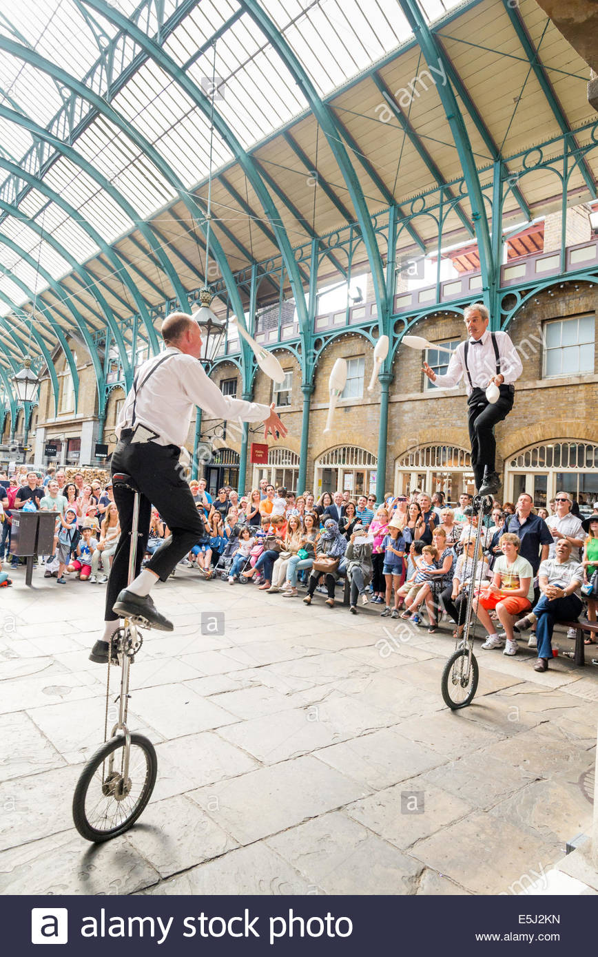Juggling unicycle performers in Covent Garden, London, England, UK - Stock Image