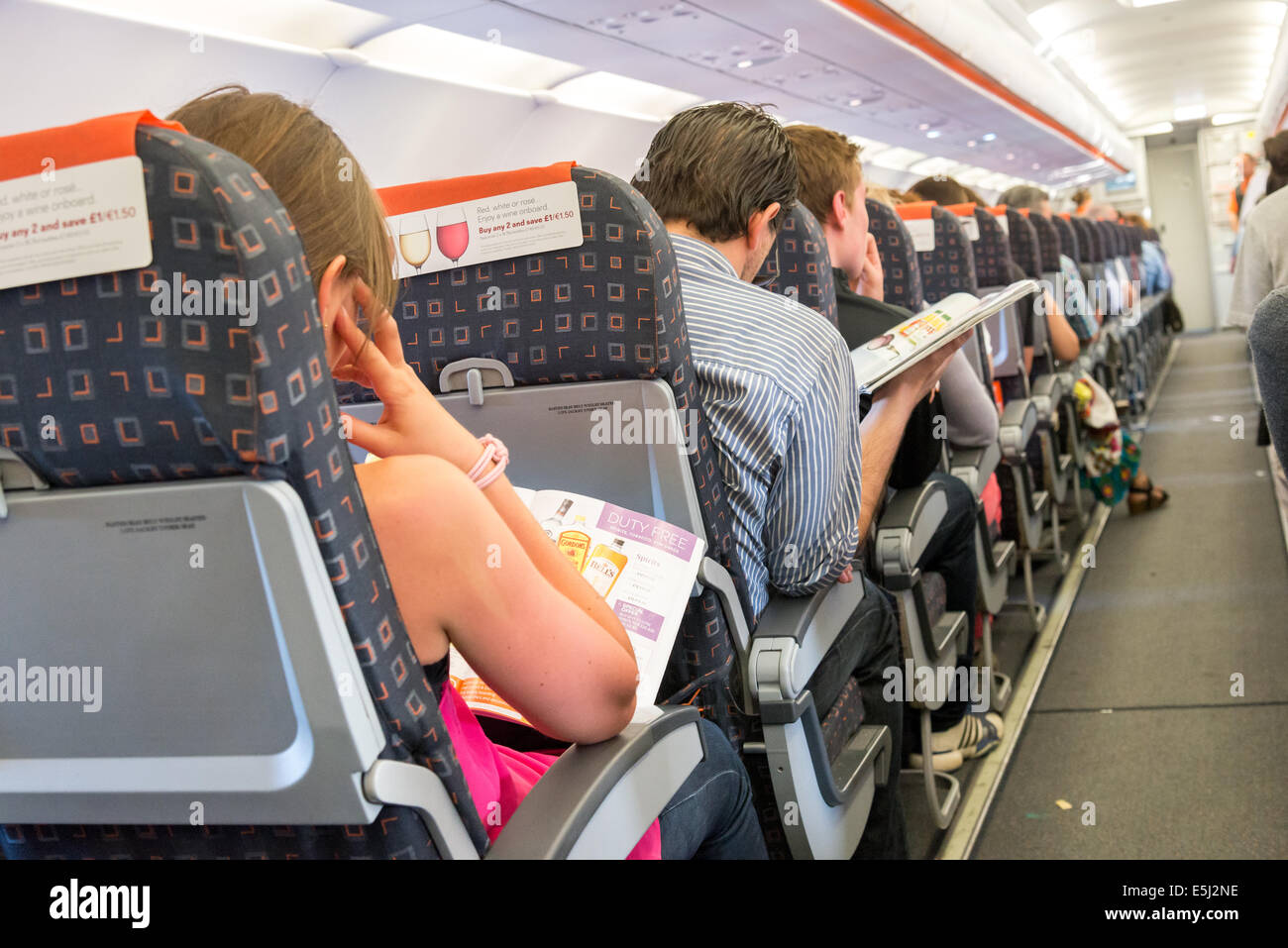 Easyjet passengers reading the inflight magazine duty free offers - Stock Image