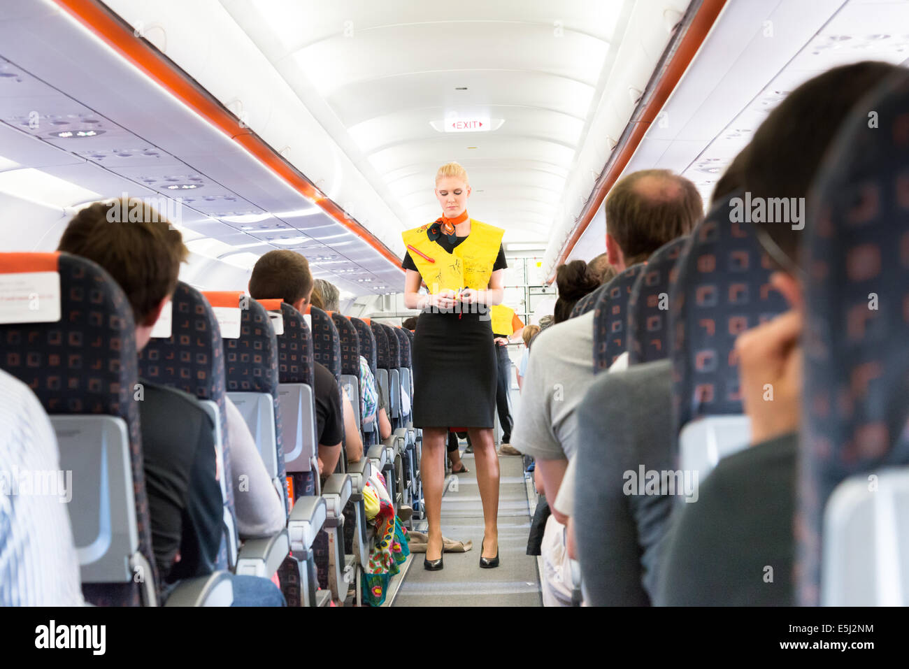 EasyJet cabin crew demonstrating use of lifejacket during safety procedure - Stock Image