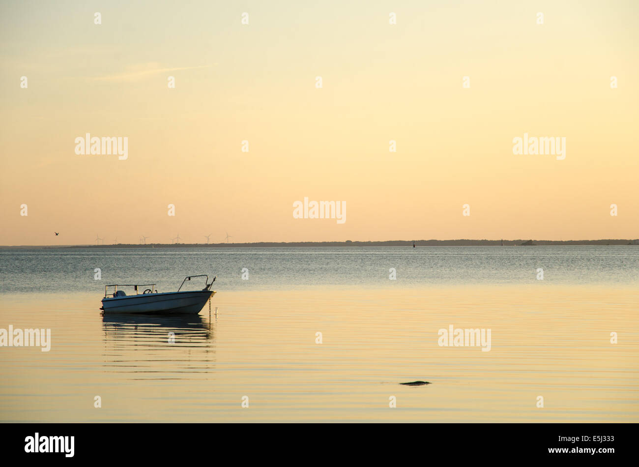 Lone anchored boat at sunset with soft colored sky - Stock Image