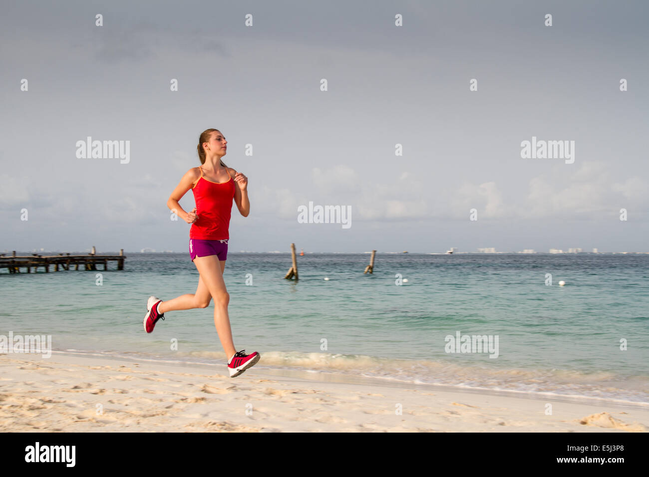 Young healthy woman running at the beach in short pants Stock Photo