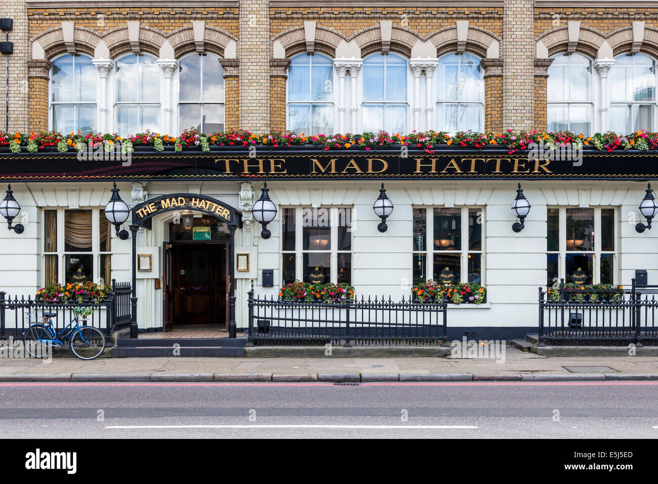 'The Mad Hatter' - a traditional English pub with Summer flower baskets in Southwark, London, UK - Stock Image
