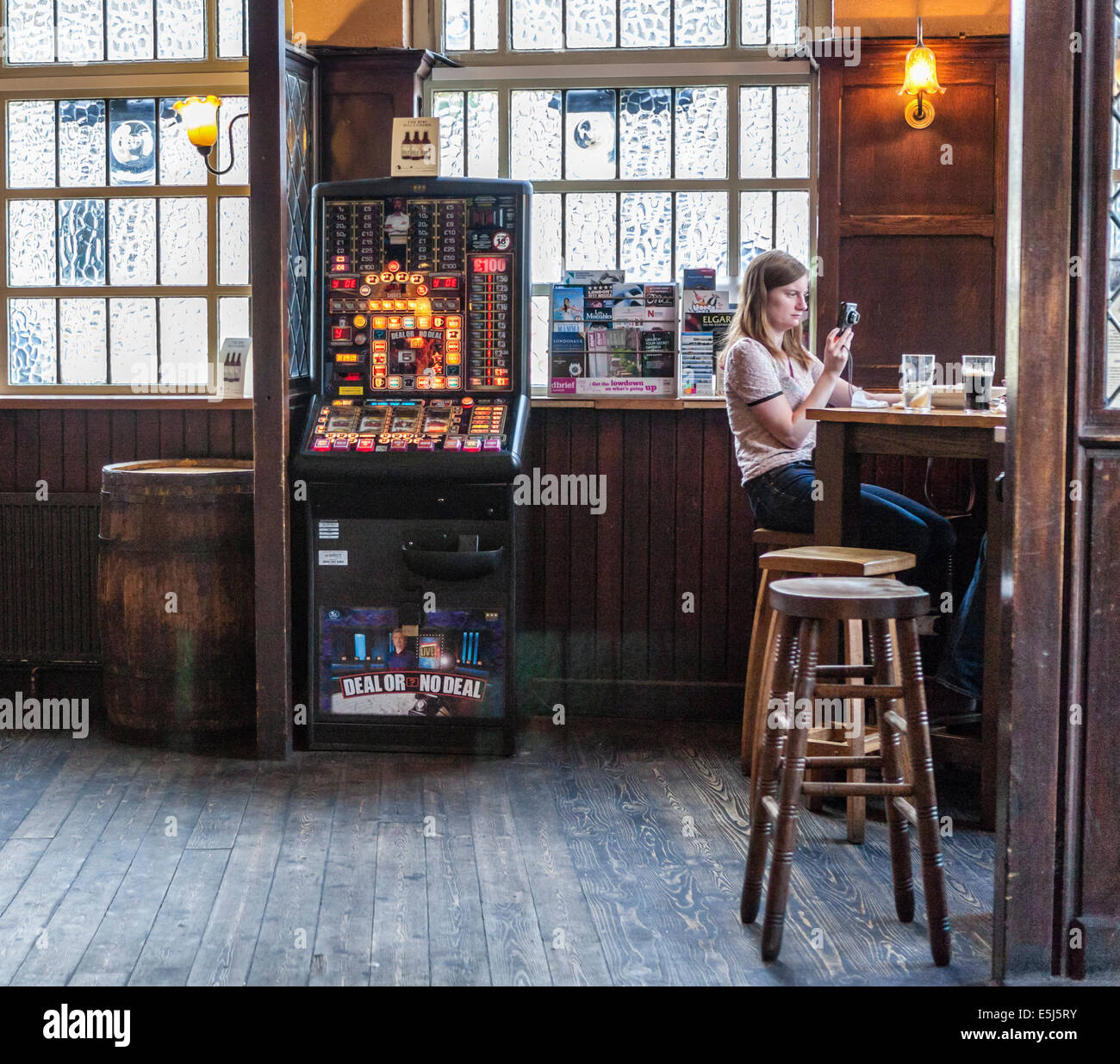 'The Market Porter' interior - inside a traditional London pub with gaming machine and woman sitting on - Stock Image