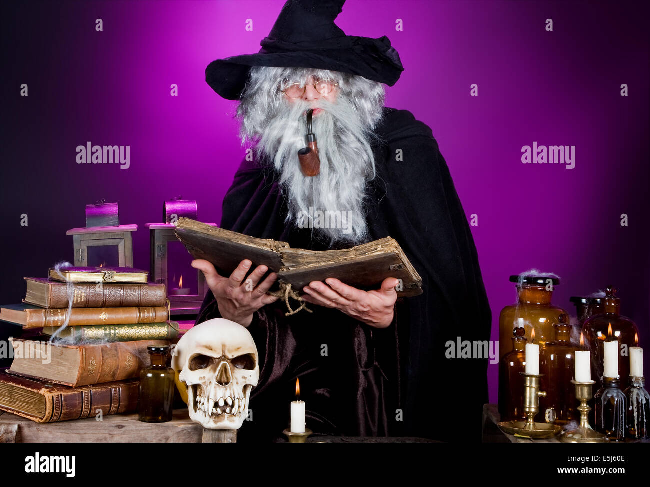 Old halloween wizard reading a spell book in his kitchen - Stock Image